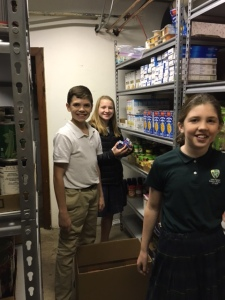 Little Flower students help to stock the food pantry with their donations.